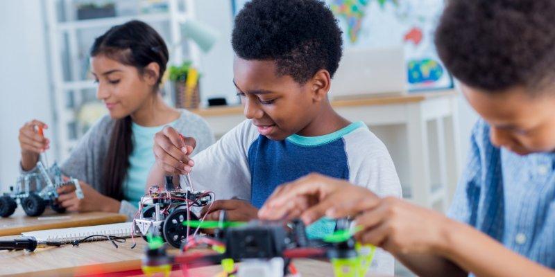 A imagem mostra três crianças sentadas em suas classes em uma sala de aula. Cada uma está mexendo em um robô de lego.